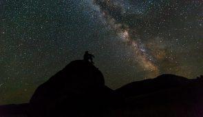 Silhueta de homem sentado em colina olhando para o céu estrelado (Foto: Banco de Imagens)