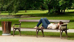 Moça deitada em um banco de praça (Foto: Banco de Imagens)