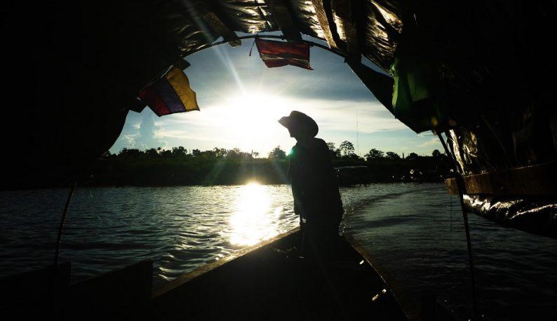 Imagem de barqueiro contra a luz do sol, passando por um túnel. No barco, estão bandeiras do Brasil, do Peru e da Colômbia (Foto: Banco de Imagens/Mauricio Goméz Quintero)