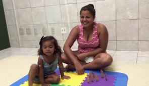Mãe e filha sentadas sobre uma esteira de EVA no chão. Ambas estão sorrindo (Foto: Reprodução/UFCTV)