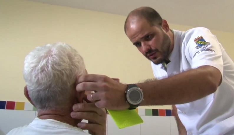 Médico tocando a orelha de um paciente idoso, que está de costas (Foto: Reprodução da UFC TV)