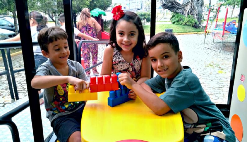 Dois meninos e uma menina sentados em uma mesa infantil amarela, brincando com peças de montar (Foto: Marília Torres)