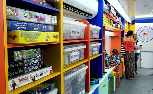 Espaço interior do ônibus com estantes coloridas preenchidas com caixas de brinquedo (Foto: Marília Torres)