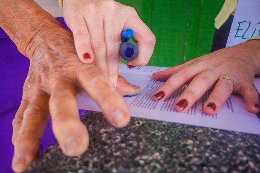Close da mão de um morador rural sendo segurada pela mão de uma pesquisadora, que carimba suas digitais (Foto: Nucom)