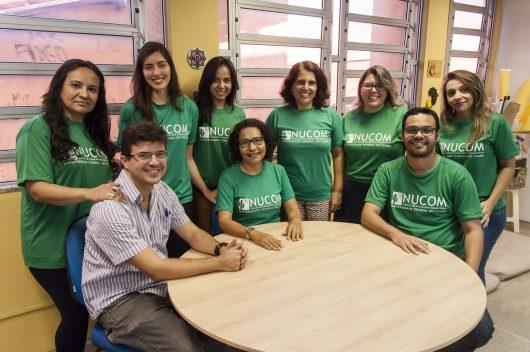 Integrantes do Nucom sentados à mesa, vestindo a blusa personalizada do grupo (Foto: Viktor Braga/UFC)
