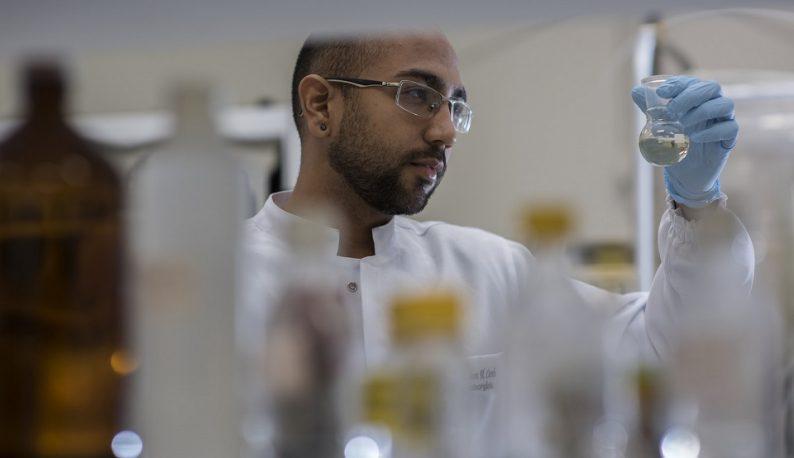 Pesquisador em laboratório segurando um tubo, com medicamentos sem foco em primeiro plano (Foto: Jr. Panela/UFC)
