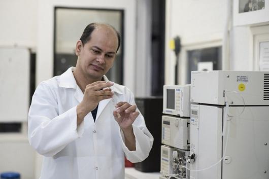 Professor Eduardo Henrique com seringa de isoniazida na mão, em laboratório (Foto: Jr. Panela/UFC)