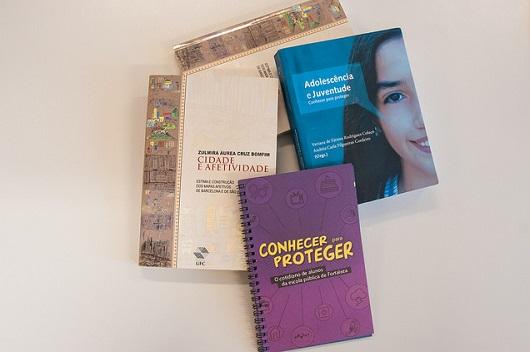 Livros sobrepostos uns aos outros e sobre a mesa (Foto: Ribamar Neto/UFC)
