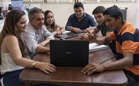 Grupo reunido na mesa, conversando e analisando a tela do computador (Foto: Jr. Panela/UFC)