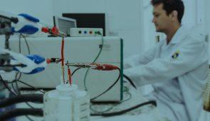 Equipamentos de eletroquímica aplicados em amostra líquida, com pesquisador ao fundo (Foto: Ribamar Neto/UFC)