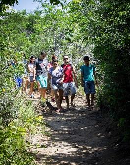 Estudantes caminham em trilha entre árvores (Foto: Mozart Lucena)