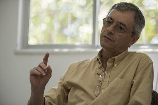 Professor Renato Sílvio sentado e levantando o braço em tom de explicação (Foto: Jr. Panela/UFC)