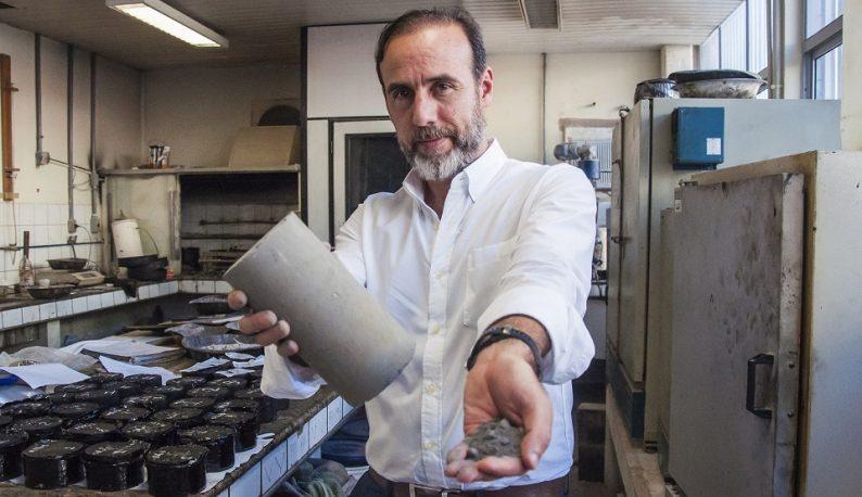 Prof. Jorge Soares mostra cinzas das termelétricas em uma mão e o bloco utilizado na construção na outra (Foto: Ribamar Neto/UFC)