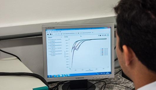 Pesquisador em frente a computador vê gráficos de linhas que sinalizam qual o tipo de contaminante presente em amostra líquida (Foto: Ribamar Neto/UFC))