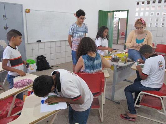 Jovens e crianças em torno de mesas, desenhando e pintando (Foto: Blog Divulgando a Extensão)