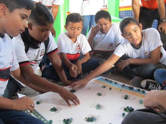 Crianças sentadas no chão em torno de um jogo de tabuleiro com bolas de gude (Foto: Blog Divulgando a Extensão)