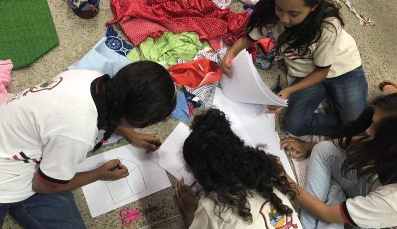 Crianças sentadas no chão em torno de papéis, onde elas desenham (Foto: Blog Divulgando a Extensão)