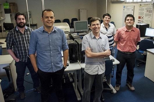 Cinco pesquisadores posando para a foto em uma sala com vários computadores (Foto: Viktor Braga/UFC)