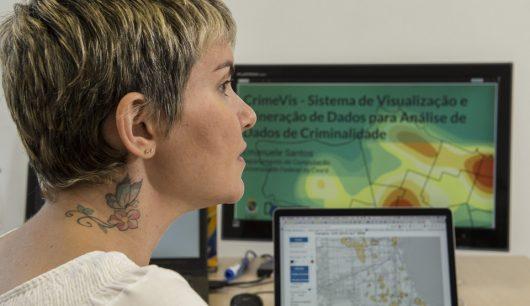 Profª Emanuele Santos em frente a mapa em tela de computador (Foto: Júnior Panela/UFC)