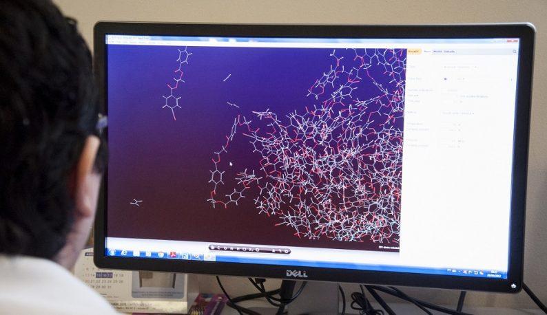 Homem usando computador, que mostra na tela uma imagem em tons roxos de moléculas químicas (Foto: Viktor Braga/UFC)