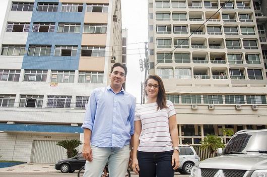 """O professor e a professora em frente a dois prédios, que formam um """"corredor"""" atrás deles (Foto: Ribamar Neto/UFC)"""