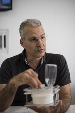 Professor Alberto Nunes sentado à mesa e segurando um equipamento para distribuição de ração (Foto: Jr. Panela/UFC)