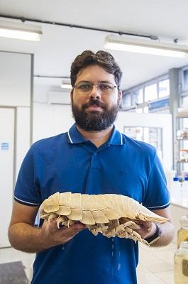 Professor Luís Ernesto Bezerra segurando um exemplar de barata-do-mar (Foto: Ribamar Neto/UFC)