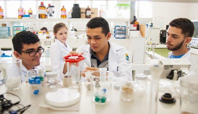 Jovens pesquisadores em bancada de laboratório, manuseando frascos (Foto: Ribamar Neto/UFC)