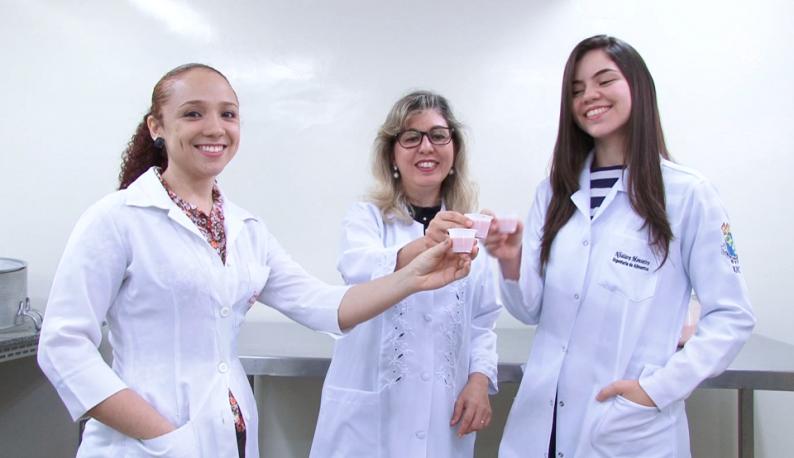 Três pesquisadoras com jalecos brindando com um pequeno copo de quefir (Foto: Divulgação/UFC TV)
