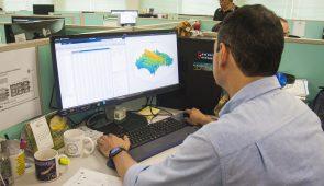 Pesquisador de costas, sentado na mesa de trabalho e usando o computador, que contém um mapa hídrico (Foto: Ribamar Neto/UFC)