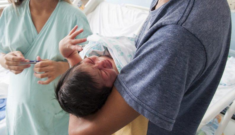 Recém-nascido nos braços de um rapaz, com uma enfermeira ao fundo (Foto: Viktor Braga)