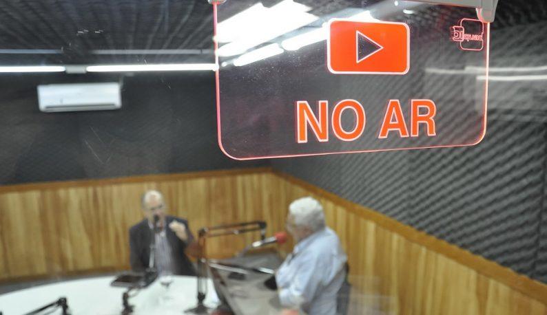 """Estúdio de rádio, com duas pessoas ao microfone. O foco está na placa de """"No Ar"""" (Foto: Guilherme Braga/UFC)"""
