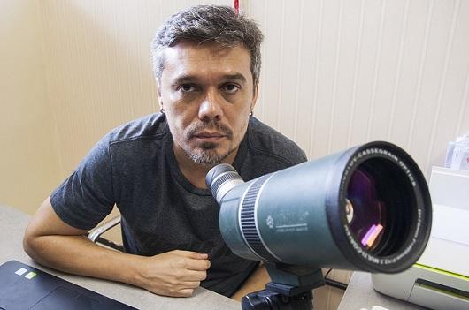 Professor Daniel Brito de Freitas atrás de um pequeno telescópio (Foto: Ribamar Neto/UFC)
