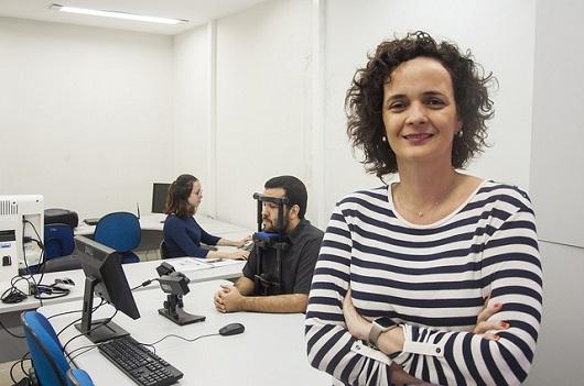 Profª Elisângela Teixeira, de brazos cruzados. Ao fundo, homem usa equipamento de eye tracking (Foto: Ribamar Neto)