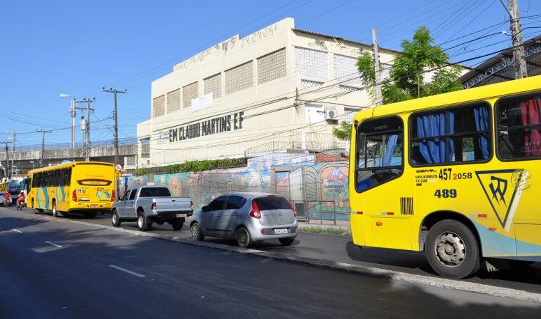 Ônibus, carros e motocicletas passando em uma avenida, em frente a uma escola de ensino fundamental (Foto: Prof. Ivan Ary Júnior/UFC)