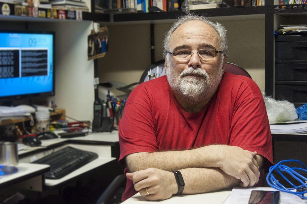 O Prof. Mário Azevedo sendo em posição frontal, em uma sala com livros e um computador (Foto: Viktor Braga/UFC)