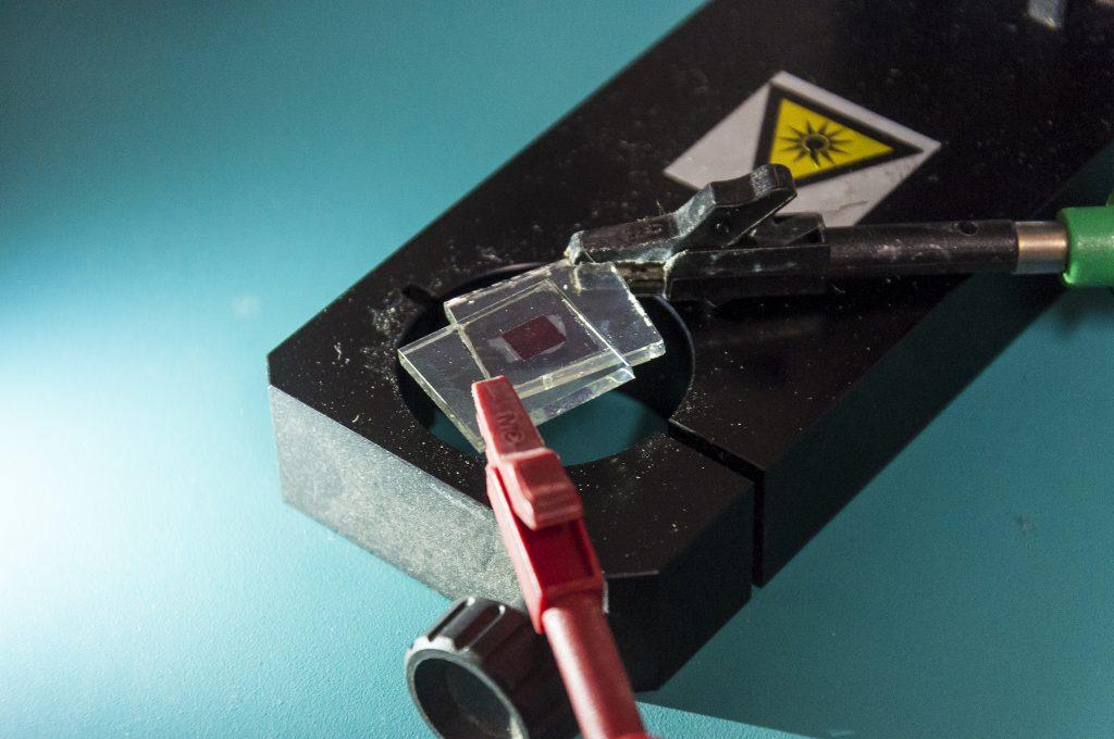 Vidros com células fotovoltaicas sensibilizadas por corante, sobre um equipamento utilizado na pesquisa (Foto: Viktor Braga/UFC)