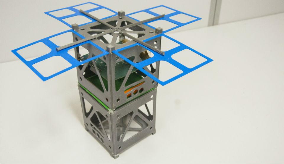 Modelo do nanossatélite, composto por dois cubos de 10 centímetros cúbicos e espaço para painéis solares, colocado sobre uma mesa (Foto: Ribamar Neto/UFC)