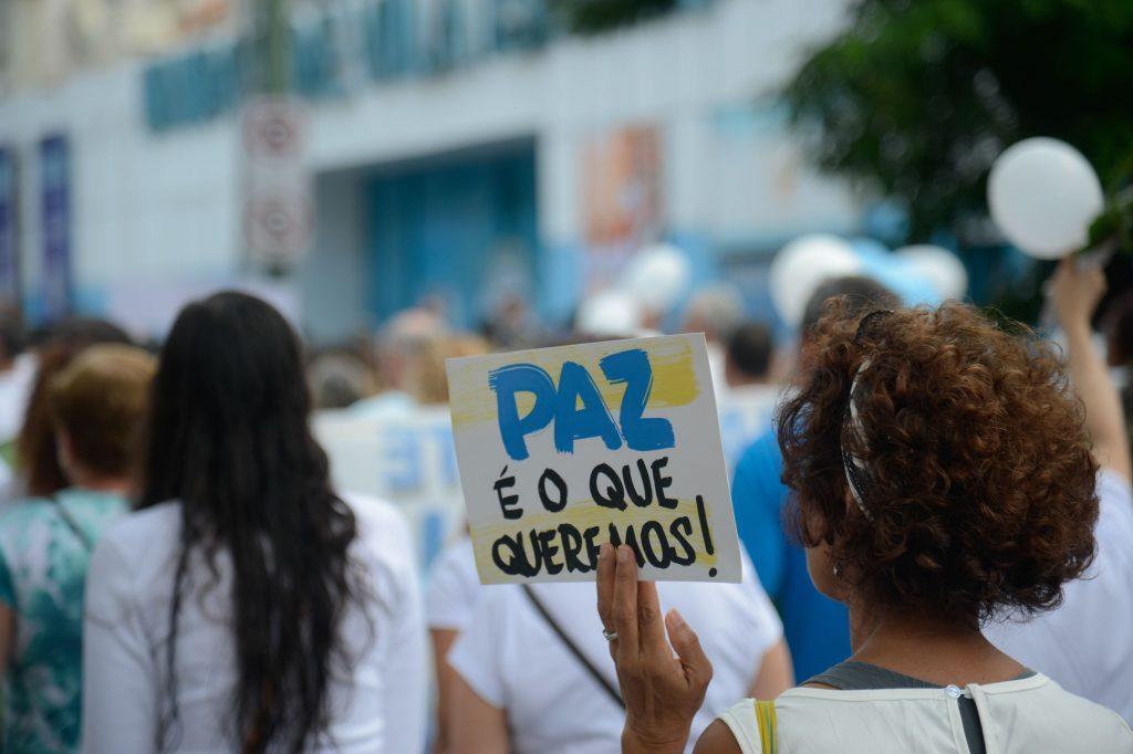 """Mulher de costas, durante passeata de rua, segurando uma placa com a mensagem """"paz é o que queremos"""" (Foto: Fernando Frazão/Agência Brasil)"""