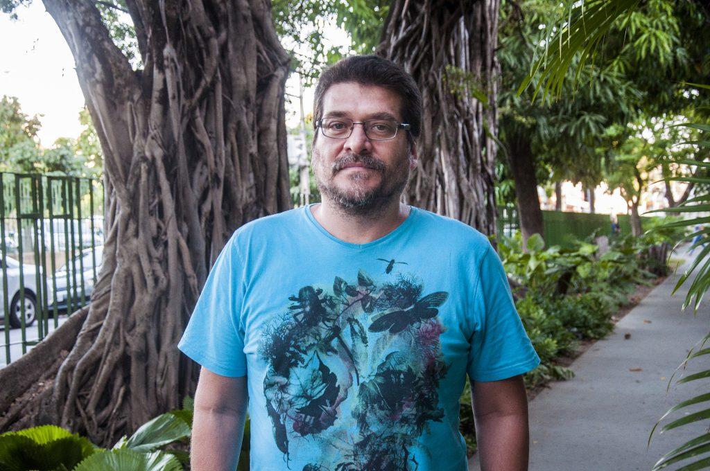 Professor Leonardo Sá, em foto de busto e rosto, em um jardim localizado na área 3 do Centro de Humanidades da UFC (Foto: Ribamar Neto/UFC)