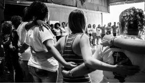 Grupo de mulheres abraçadas de costas, formando uma espécie de cordão humano (Foto: Rosilene Miliotti/FASE)