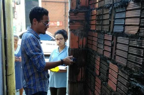 Estudantes fazendo medição do muro de uma casa, com uma senhora próximo, acompanhando o trabalho (Foto: Divulgação/ETECS)