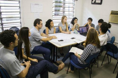 O coordenador do projeto e os estudantes ao redor de uma mesa, sentados, com projetos em papel que estão sobre a mesa (Foto: Ribamar Neto/UFC)