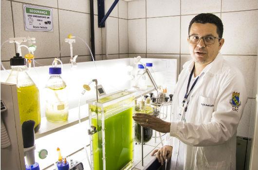 Professor André Luis Coelho ao lado de um equipamento no qual há microalgas dentro (Foto: Ribamar Neto/UFC)