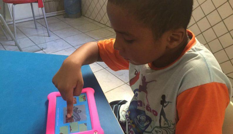 Menino sentado em uma mesa mexendo em um tablet rosa