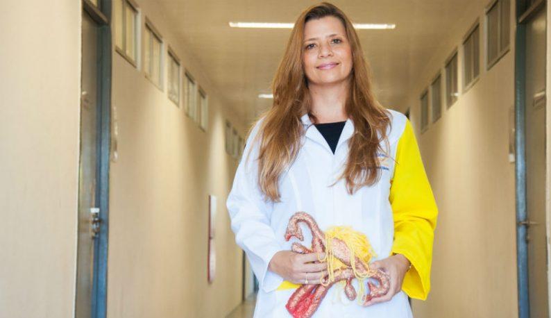 Professora Tatiana Zylberberg em um corredor segurando um peça anatômica que reproduz um útero (Foto: Viktor Braga/UFC)