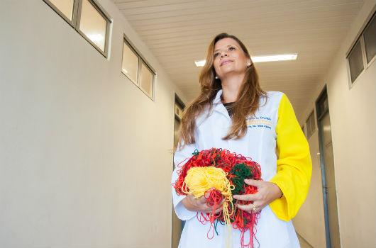 Professora em um corredor segura um novelo nas cores vermelha, amarela e verde (Foto: Viktor Braga/UFC)
