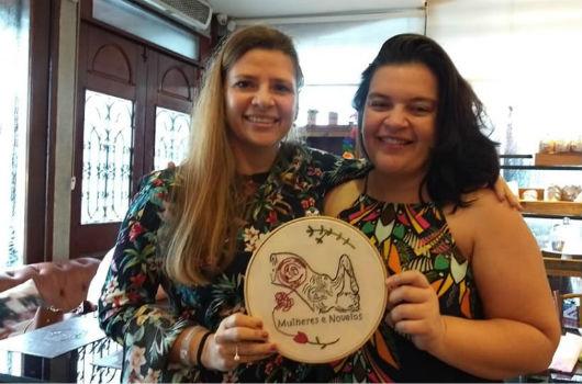 As professoras Tatiana Zylberberg e Halana Brandão seguram um bordado alusivo ao projeto Mulheres e Novelos (Foto: Arquivo pessoal)