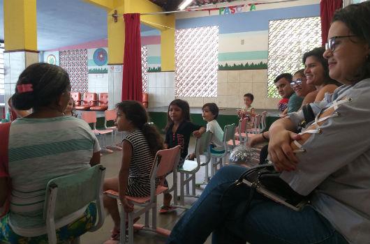 Crianças e seus familiares sentados em cadeiras durante momento de atividades no IPREDE (Foto: Clarice Nascimento/PREX-UFC)