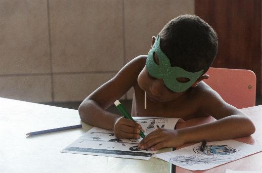 Menino sentado fazendo desenho e pintura em uma folha de papel que está sobre uma mesa (Foto: Viktor Braga/UFC)